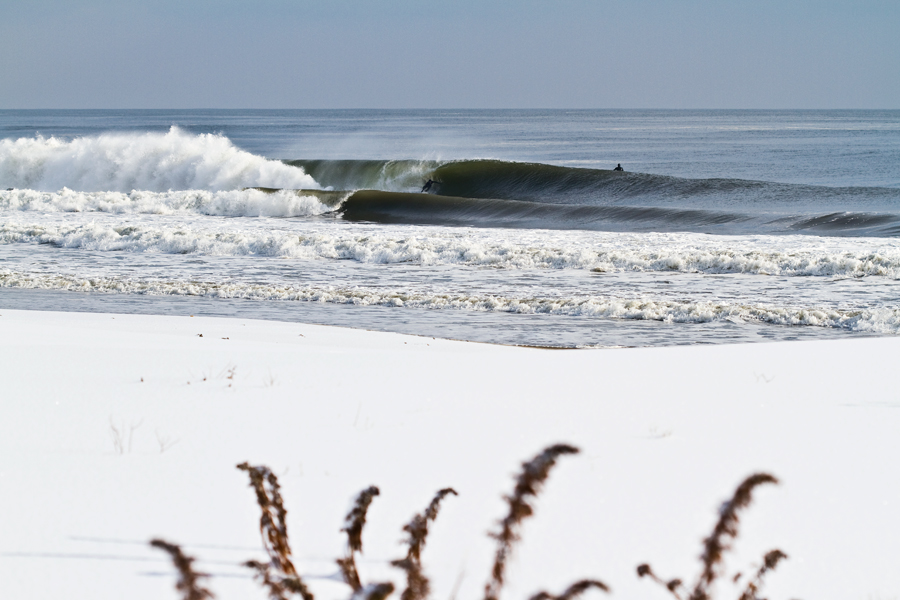 snow surf. surf photographer. breaking wave. snow on the beach. foreground. digital photography.